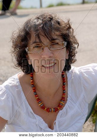 a portrait of a middle-aged brunette woman with eyeglasses outdoor