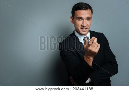 Successful businessman. Thoughtful nice confident businessman talking to you and gesticulating while standing against grey background