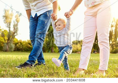 The first steps of the baby. Parents are teaching their child to walk. A happy family.