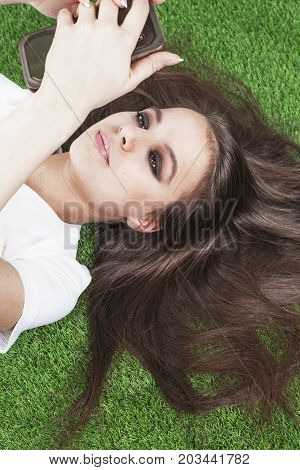 Disconcerted Beautiful Lady Lies On The Grass Using A Smart Phone On The Grass. Smart Girl With Long
