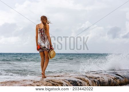 Woman with a hat in her hands staring at the sea at Playa del Carmen beach Quintana Roo Mexico.