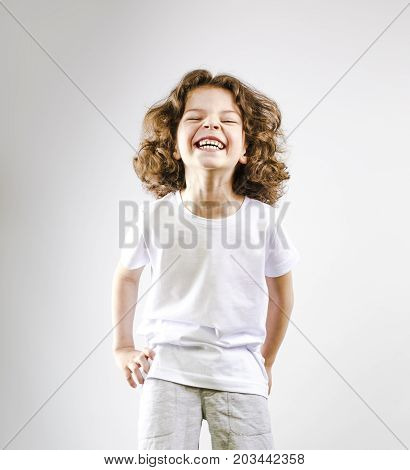 Surprised Boy Laughing Out Loud On A Gray Background.
