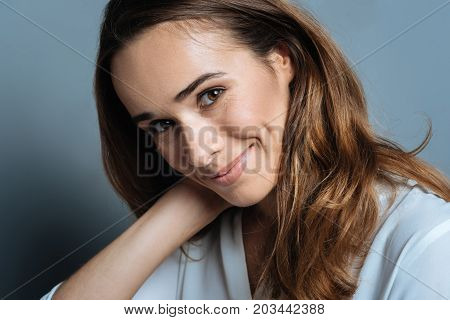 I am shy. Nice pleasant cheerful woman putting her hand behind the neck and smiling while being shy