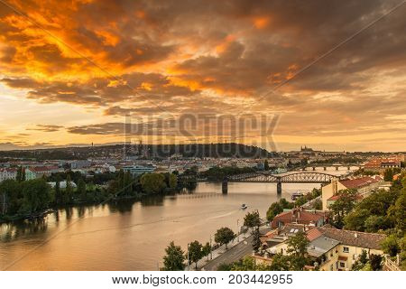 Sunset over Vltava river with Railway bridge and Prague castle in the background. Orange moody sky with dramatic clouds. Summer twilight in Prague Czech Repubic