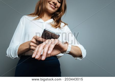 Synchronizing time. Nice delighted pretty woman looking at her watch and smiling while synchronizing time with her smartphone