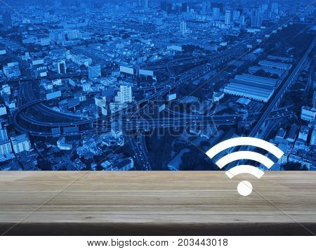 Wi-fi button on wooden table over modern city tower street and expressway Technology and internet concept