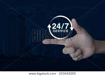 24 hours service icon on finger over world map and modern city tower Full time service concept Elements of this image furnished by NASA