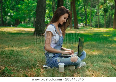 charming young lady sitting on the grass and prints on a laptop