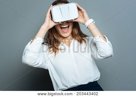 Emotional person. Delighted positive happy woman wearing 3d glasses and expressing her emotions while being in a new reality