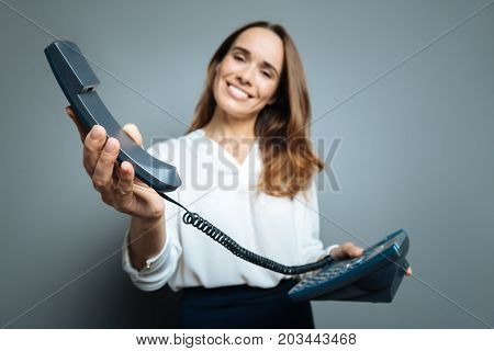 Its for you. Selective focus of a telephone receiver being held by a nice pleasant friendly woman while being given to you