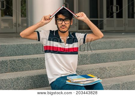 young funny guy sitting on the street and keeps a book on your head