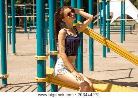 beautiful slender sport girl sits on a side street near Chinning bars