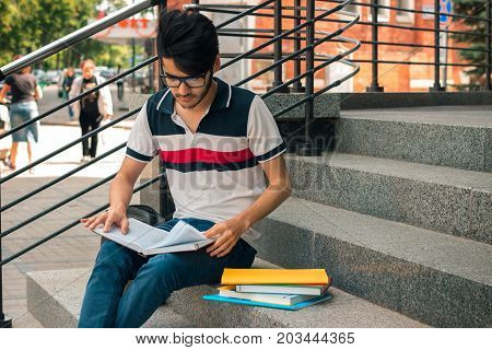 young stylish guy with books sitting on the stairs