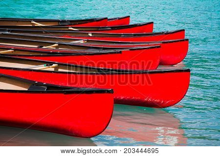 Row of red canoes in lake calm water