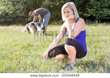 Young blond woman is bored while her partner is playing with dogs in the background.
