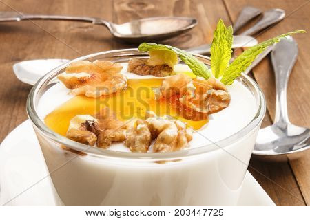 greek yogurt with walnut and acacia honey in a glass