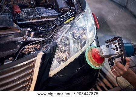 Polishing the headlights on a black car with the help of power tools for maintenance.