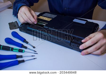 close up picture of hands and broken notebook, men repair laptop