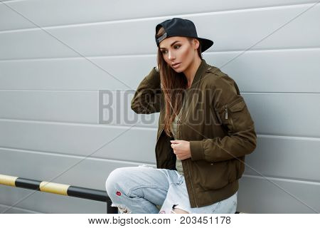 Fashionable Young Woman With Freckles In Stylish Street Clothes With A Baseball Cap Sits Near A Meta