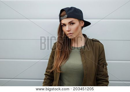 Street Portrait Of A Beautiful Woman With Freckles In A Baseball Cap In A Military Jacket Near A Met
