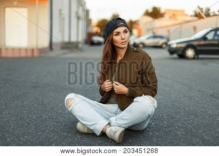 Beautiful Young Woman With Freckles In A Fashionable Jacket And Blue Ragged Jeans Sits On The Asphal