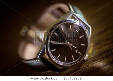 Luxury watch with black dial and leather watch band.