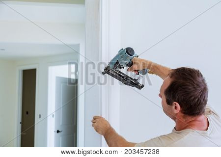 Carpenter Brad Using Nail Gun To Moldings On Doors, That All Power Tools Have On Them Shown Illustra