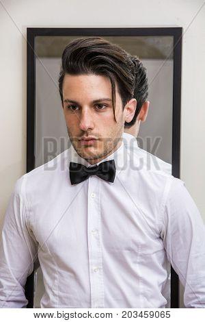 Mirror reflection of elegant handsome man wearing bow-tie