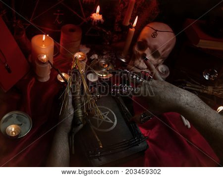 Witch's hands carrying out a ritual with Voodoo doll, candles, magic book, crystal, amulets and pentagram symbol. Halloween concept, black magic ritual.