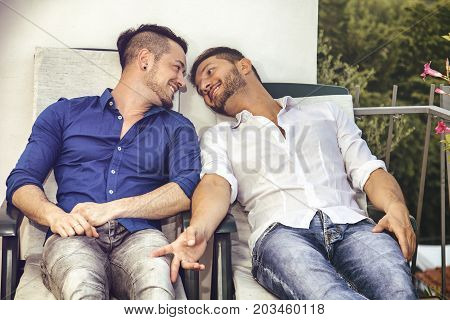 Two gays sitting on chairs at balcony holding hands and looking at each other.