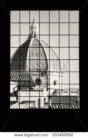 Cattedrale di Santa Maria del Fiore behind the window Florence Tuscany Italy. Black and white photo.