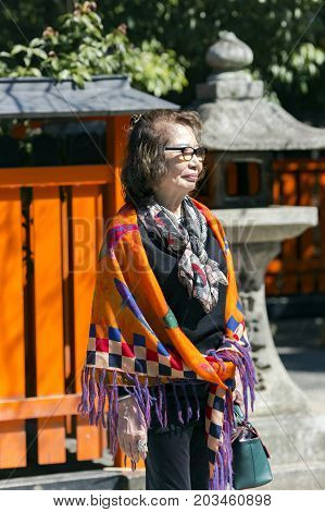 JAPAN, KYOTO, APRIL, 06, 2017 - Mature Japanese woman in bright shawl at the temple of Fushimi Inari Taisha, Kyoto, Japan. In Japan domestic tourism is well developed, many elderly people visit temples.