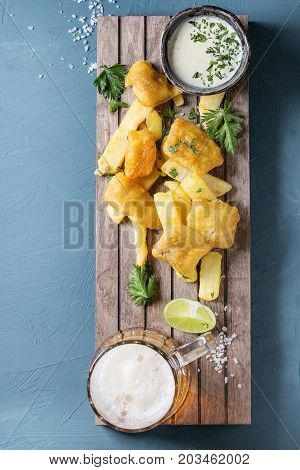 Traditional british fast food fish and chips. Served with white cheese sauce, lime, parsley, glass of lager beer on wooden serving board over blue concrete background. Top view, copy space
