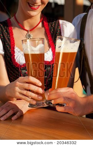 Couple in traditional Bavarian Tracht - Dirndl and Lederhosen - in a beer tent at the Oktoberfest or in a beer garden clinking glasses with whet beer, only glasses and torsos to be seen