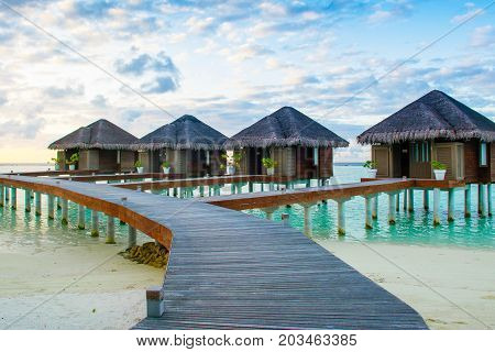 Dhidhoofinolhu Maldives - 5 July 2017: Sunset landscape onthe sandy beach. Over water wooden bungalow in luxury resort on the Indian Ocean Maldives 5 July 2017