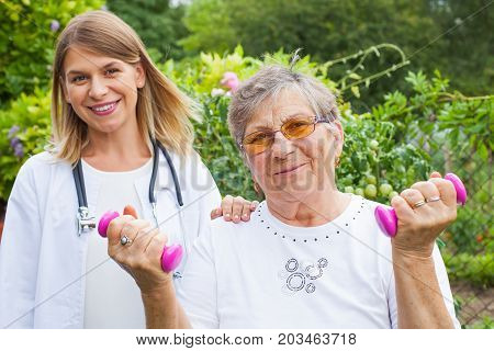 Elderly female doing fitness exercises with dumbbells assisted by smiling medical doctor
