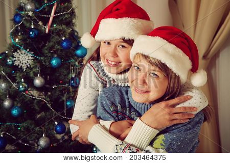 happy mother and daughter in santa hat near Christmas tree. New Year and xmas people