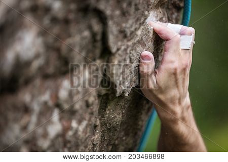 Closeup view of rock climber's hand gripping hold on natural cliff