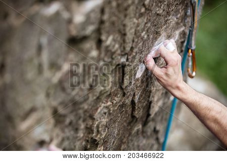 Rock climber's hand gripping small hold on natural cliff hand in focus