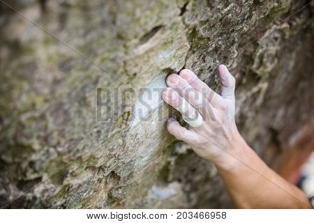 Rock climber's hand gripping small hold on natural cliff shallow depth of field