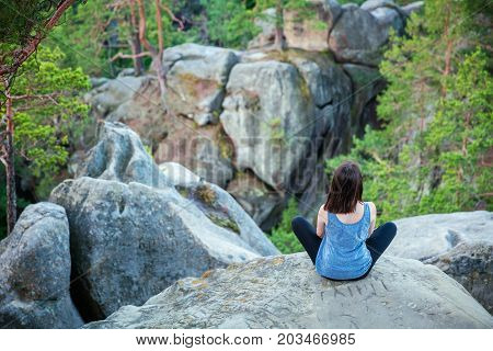Young girl sitting on top of cliff and watching rocky landscape beneath