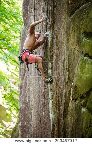 Young male rock climber on challenging route on vertical cliff gripping small handholds