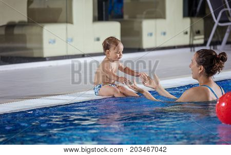Young woman catching little son sitting poolside in indoor swimming pool