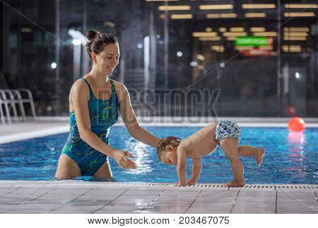 Young woman playing with little son by poolside in indoor swimming pool