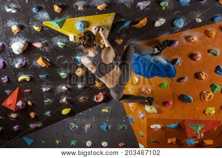 Caucasian young woman bouldering in climbing gym