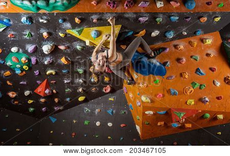 Young woman bouldering in climbing gym looking at camera and smiling while hanging upside down
