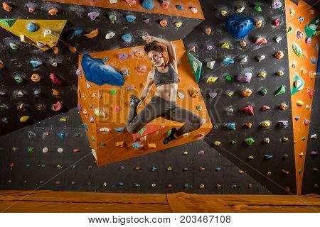Pretty young woman jumping in climbing gym against wall with holds