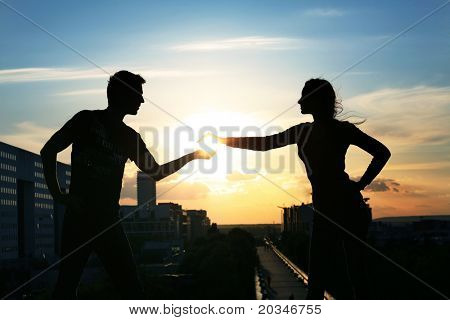 Young handsome couple over evening city background
