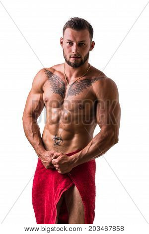 Handsome shirtless muscular man, standing, in studio shot with towel around his waist, isolated on white