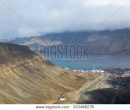 View of Longyearbyen from the top of Sarkofagen mountain in Svalbard archipelago. Longyear river running in the valley into Adventfjorden. Beautiful light on side of mountain and low clouds covering the opposite Hiorth mountain